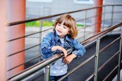 牛仔裤夹克的一个小女孩 免版税图库摄影