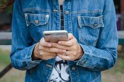牛仔裤夹克的女孩使用巧妙的电话 免版税图库摄影