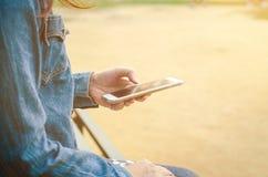 牛仔裤夹克的女孩使用聪明的phonea 免版税库存照片