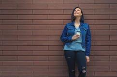 牛仔裤夹克的年轻笑的女孩在一个棕色砖墙附近与 库存照片