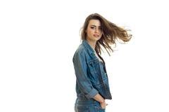 牛仔裤夹克神色的逗人喜爱的女孩到照相机里和她的头发通过空气飞行 库存照片