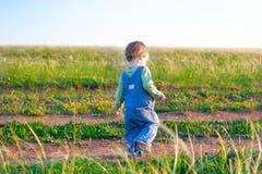 牛仔裤工作服步行的孩子在土路 免版税库存图片