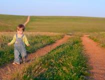 牛仔裤工作服的甜孩子去土路 免版税库存图片