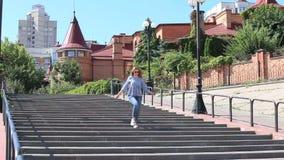 牛仔裤的一个俏丽的女孩在一个宽楼梯走 股票视频