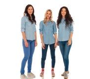 牛仔裤的三名年轻偶然妇女一起给身分穿衣 免版税图库摄影