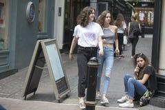 牛仔裤的两个女孩通过女孩坐边路 免版税库存照片