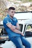 牛仔裤的人,坐一辆老损坏的汽车 免版税库存照片