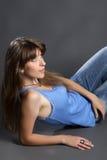 牛仔裤的俏丽的妇女微笑和坐地板 库存照片
