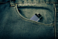 牛仔裤的口袋有打火机的 布料背景 定调子 免版税库存图片