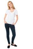 牛仔裤的可爱的微笑的妇女 图库摄影