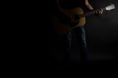 牛仔裤的吉他弹奏者在框架的右边弹一把声学吉他,在黑背景 水平的框架 免版税库存图片