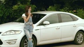 牛仔裤的女孩在一个美丽的机器附近穿戴立场并且发表演讲关于移动电话 影视素材