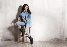 牛仔裤的女孩坐木椅子 图库摄影
