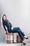 牛仔裤的女孩坐金属桶 库存图片