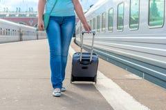 牛仔裤的女孩带着在火车平台的一个手提箱 免版税图库摄影