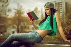 牛仔裤的女孩读书的在长凳 库存照片