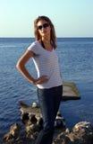 牛仔裤的女孩临近海 图库摄影