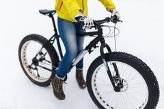 牛仔裤的妇女在自行车 免版税库存图片