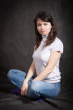 牛仔裤的妇女坐地板 库存图片