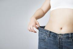牛仔裤的少妇大号,减重的概念 免版税库存照片