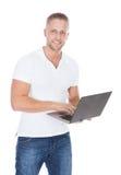 牛仔裤的微笑的人使用便携式计算机 库存照片