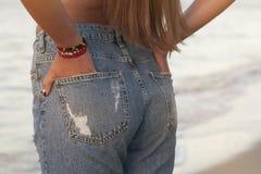 牛仔裤的性感的完善的妇女反对海 回到视图 中间身体局部 方式 时兴的牛仔裤广告  库存图片
