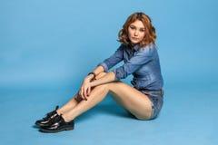 牛仔裤的性感的成人女孩佩带坐蓝色背景 免版税库存照片