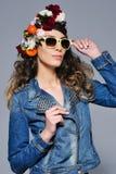 牛仔裤的成套装备和太阳镜愉快的妇女 免版税图库摄影