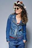 牛仔裤的成套装备和太阳镜愉快的妇女 免版税库存图片