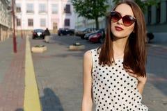 牛仔裤的有太阳镜的短上衣小点衬衣走在一个晴朗的城市的美丽的女孩, 免版税库存照片