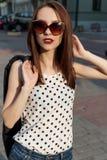 牛仔裤的有太阳镜的短上衣小点衬衣走在一个晴朗的城市的美丽的女孩, 库存图片