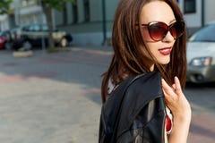 牛仔裤的有太阳镜的短上衣小点衬衣走在一个晴朗的城市的美丽的女孩, 免版税库存图片