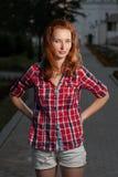 牛仔裤的短裤和摆在红色的衬衣的姜头发的妇女户外 免版税库存照片