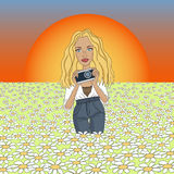 牛仔裤的美丽的女孩有在日落的一台照相机的,拍摄春黄菊花  免版税库存图片