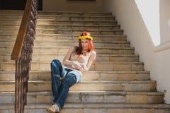 牛仔裤的美丽的性感的可爱的年轻女性有在他的头的一个花圈的在大厦台阶 图库摄影