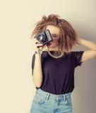牛仔裤的美丽的年轻性感的妇女有一台照相机的在卷发在演播室,减速火箭的过滤器的手上 免版税库存照片