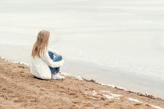 牛仔裤的美丽的年轻白肤金发的女孩和一件白色衬衣坐湖的冻结的寒冷的岸在伯爵的森林附近 库存照片