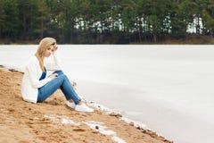 牛仔裤的美丽的年轻白肤金发的女孩和一件白色衬衣坐湖的冻结的寒冷的岸在森林附近 免版税库存图片