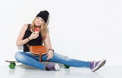 牛仔裤的,运动鞋,帽子年轻美丽的快乐的时尚女孩坐与葡萄酒袋子的一longboard在她的肩膀和吃集成电路 免版税库存照片