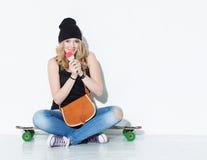 牛仔裤的,运动鞋,帽子年轻美丽的快乐的时尚女孩坐与葡萄酒袋子的一longboard在她的肩膀和吃集成电路 免版税图库摄影