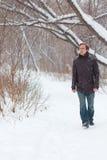 牛仔裤的年轻严肃的人在森林里走在冬天 免版税图库摄影