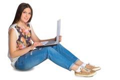 牛仔裤的年轻微笑的妇女有膝上型计算机的坐地板 免版税库存照片