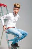 牛仔裤的年轻男孩和白色衬衣在梯子上升 免版税库存图片