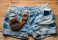 牛仔裤短裤和巧妙的电话在木地板上 库存图片