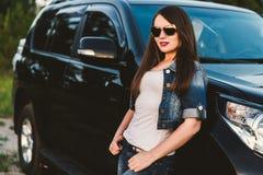 牛仔裤衣裳和玻璃的一个愉快的女孩在一辆大黑汽车附近站立 半身画象用手 免版税库存照片