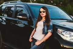 牛仔裤衣裳和玻璃的一个愉快的女孩在一辆大黑汽车附近站立 半身画象用手 免版税图库摄影