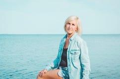 牛仔裤衬衣的白肤金发的中年妇女,坐一个海滩有蓝天背景,拷贝空间 画象有吸引力 库存照片