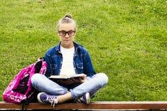 牛仔裤衬衣的美丽的白肤金发的女小学生女孩读书的在与一个背包的草在公园教育 库存图片