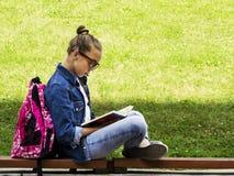 牛仔裤衬衣的美丽的白肤金发的女小学生女孩读书的在与一个背包的草在公园教育 库存照片