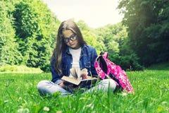 牛仔裤衬衣的美丽的白肤金发的女小学生女孩读书的在与一个背包的草在公园 免版税库存图片